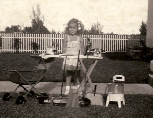 Paula, circa 1952, surrounded by the tools her parents thought important for a girl. Photo taken in front of our new tract house in Miami Springs, Florida--land carved from the eastern edge of  the Everglades.