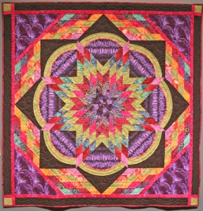 """Passionflower was an experiment in hand quilting using two threads in the eye of that tiny needle! I used a pale lavender cotton thread and a sparkly pink rayon thread to add a touch of shine to the quilting. All cotton fabrics, but featuring several purple Nancy Crow fabrics. size: 54""""x 54"""""""