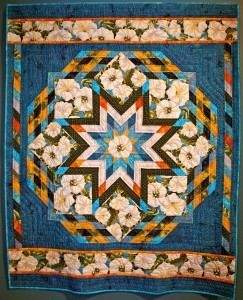 "I discovered this fabric, called ""Georgia"" in honor of the artist Georgia O' Keefe who often painted thse moonflowers, after teaching a Lone Star class at Spinning Stars. I knew I wanted to feature this fabulous fabric in the eight setting squares of a lone star. I was so enthusiastic about this new project that by the next week I had pieced the central star. After reading Ruth McDowell's book on color I was inspired to experiment with weaving color in and out to suggest transparency in the outer series of diamonds. This original design is the fouth in a series of lone star quilts from 2003. size: 59"" x 73"""